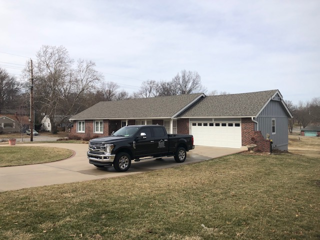 A brick house with a truck in front and a new roof installed by Buck Roofing in Kansas City