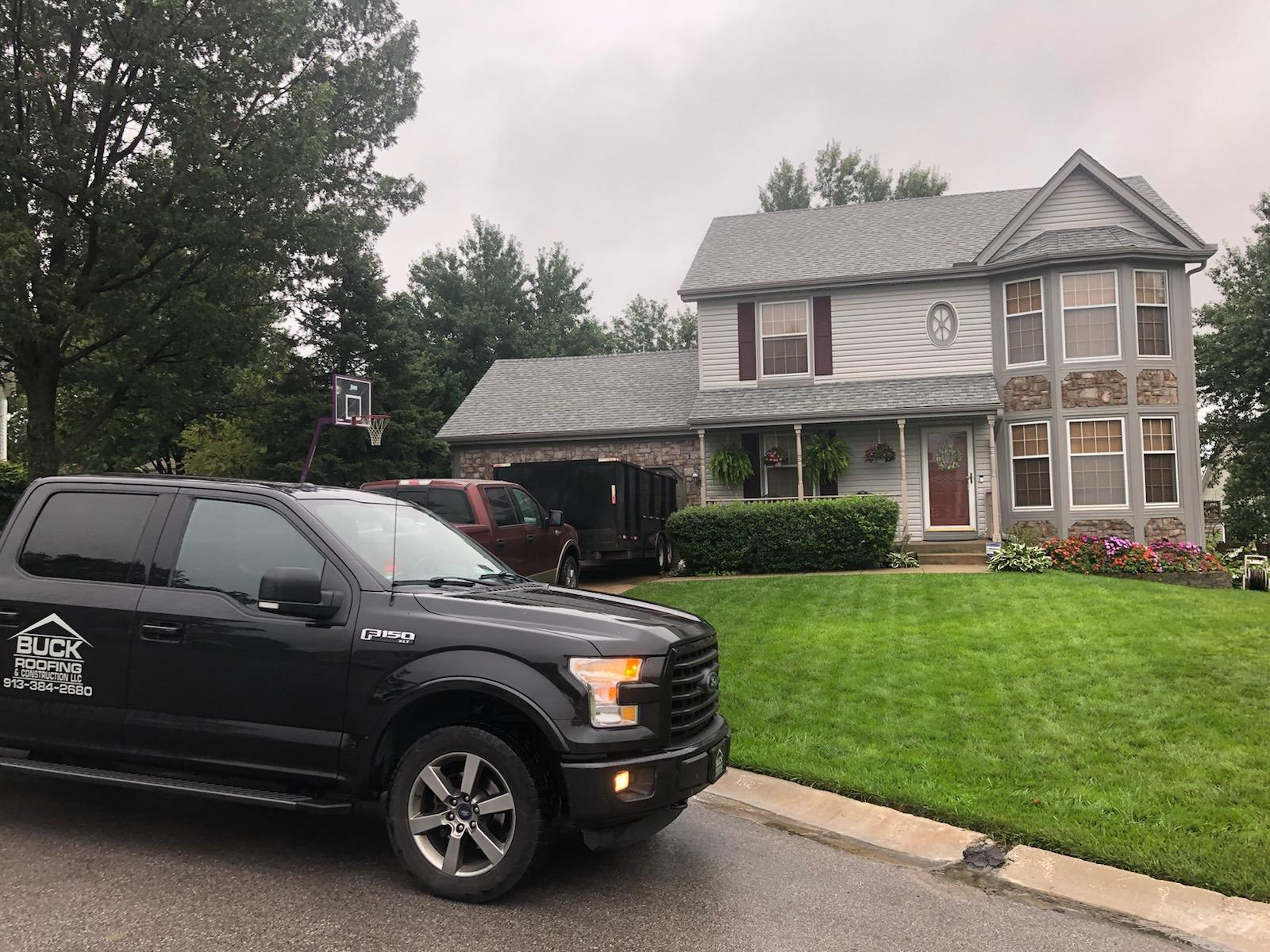 A custom gray residential roof on a house in the Kansas City area with the Buck Roofing truck parked in front
