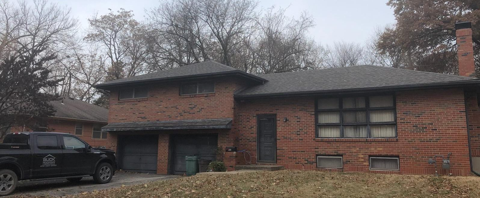 A brick house with a brand new roof from the residential roofing experts at Buck Roofing