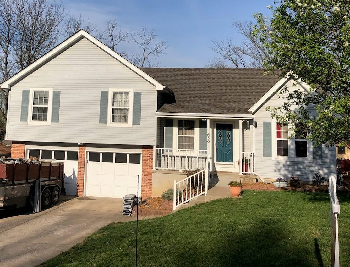 A gray house with a new roof by Buck Roofing in Kansas City