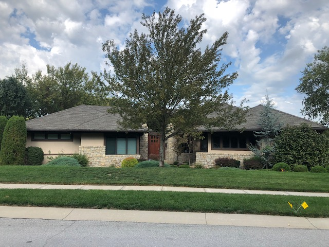 A house of stone with a new roof by Buck Roofing, Kansas City residential roofing installers