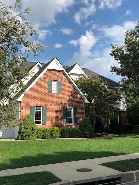 A brick and white house with a residential roof installed by Kansas City's Buck Roofing