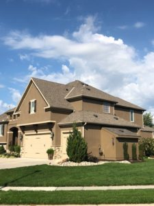 A large brown house with a quality roof by Kansas City residential roofing company Buck Roofing